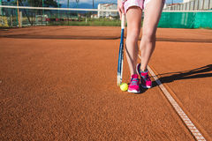 Jambes femelles avec la raquette de tennis Photos libres de droits