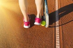 Jambes femelles avec la raquette de tennis Images stock