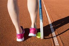 Jambes femelles avec la raquette de tennis Photos stock