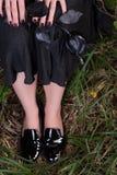 Jambes femelles dans des chaussures de cuir verni noires sur l'herbe Jupe noire et une rose Image stock