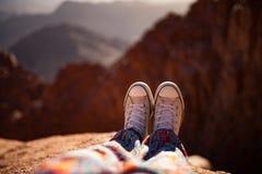 Jambes femelles dans des chaussures en caoutchouc au-dessus de falaise contre le contexte de la montagne Photographie stock