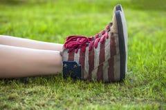 Jambes femelles dans des espadrilles avec la conception du drapeau américain dessus Images libres de droits