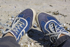 Jambes femelles dans des espadrilles bleues à l'arrière-plan du sable Photo libre de droits