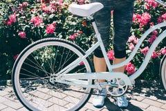 Jambes femelles dans des espadrilles bleues et une bicyclette élégante contre un CCB Image stock