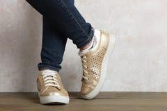 Jambes femelles dans des espadrilles d'or Photo stock