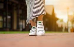 Jambes femelles dans des espadrilles de rue sur la mode de beauté de fond de tache floue Photographie stock libre de droits