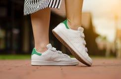 Jambes femelles dans des espadrilles de rue sur la mode de beauté de fond de tache floue Image stock