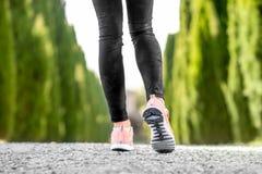 Jambes femelles dans des espadrilles de sport Photos stock
