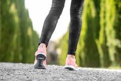 Jambes femelles dans des espadrilles de sport Photographie stock libre de droits