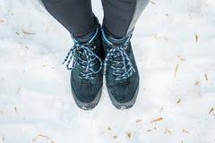 Jambes femelles dans des espadrilles de trekking sur un fond de neige dans le wint Photographie stock libre de droits