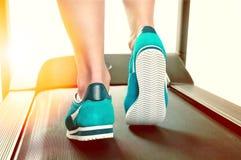 Jambes femelles dans des espadrilles de turquoise sur un tapis roulant Photo stock