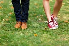 Jambes femelles dans des espadrilles rouges et jambes masculines dans des chaussures brunes Images libres de droits
