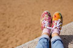 Jambes femelles dans des jeans et espadrilles florales lumineuses dans le backgro Image libre de droits