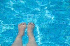 Jambes femelles dans l'eau bleue claire et transparente Images stock