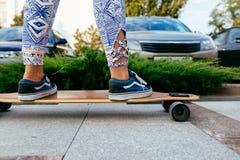 Jambes femelles dans le pantalon coloré se tenant sur le longboard Fille de Longboard sur la rue Image libre de droits