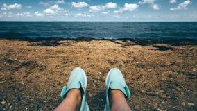 Jambes femelles dans le repos d'espadrilles sur la plage le long du concept de mer Image stock