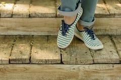 Jambes femelles dans les blues-jean et des espadrilles rayées sur la vieille chambre en bois Photos stock