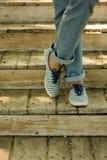 Jambes femelles dans les blues-jean et des espadrilles rayées sur la vieille chambre en bois Photo libre de droits