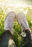 Jambes femelles dans les espadrilles blanches de toile et des jeans noirs photographie stock