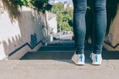Jambes femelles dans les espadrilles et des jeans Images libres de droits