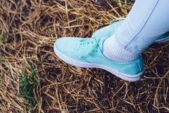 Jambes femelles dans les espadrilles et des jeans sur le fond de l'herbe sèche Image stock