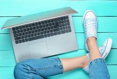 Jambes femelles dans les jeans et des espadrilles, ordinateur portable sur un plancher en bois de turquoise Technologies modernes Photo libre de droits