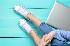 Jambes femelles dans les jeans et des espadrilles, ordinateur portable sur un plancher en bois de turquoise Technologies modernes Images stock