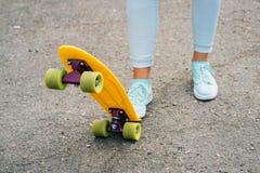 Jambes femelles dans les jeans et des espadrilles se tenant près du jaune lumineux SK Images libres de droits