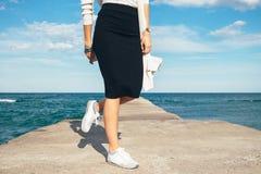 Jambes femelles dans une jupe et des espadrilles sur le fond de la mer Images stock