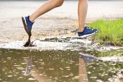 Jambes femelles de coureur fonctionnant dans la boue Photo libre de droits