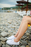 Jambes femelles de culture sur Pebble Beach Photographie stock libre de droits