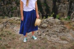 Jambes femelles de photo dans des chaussures en caoutchouc sur le fond du canyon Images libres de droits