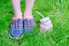 Jambes femelles en espadrilles et smoothies de fraise sur l'herbe verte Photos stock