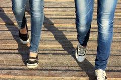 Jambes femelles en jeans et plan rapproché d'espadrilles sur le fond en bois Images libres de droits