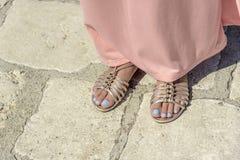 Jambes femelles en sandales sur des jambes Image libre de droits
