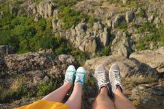Jambes femelles et masculines de photo dans des chaussures en caoutchouc sur le fond du canyon Image libre de droits