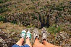 Jambes femelles et masculines de photo dans des chaussures en caoutchouc sur le fond du canyon Images libres de droits