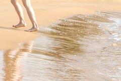 Jambes femelles marchant hors de la mer photographie stock
