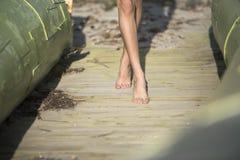 Jambes femelles minces portant le bikini et la marche Image libre de droits