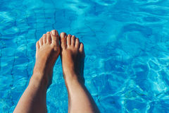 Jambes femelles nues sur un fond de l'eau bleue Photographie stock libre de droits