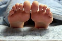 Jambes femelles, pieds sur le lit, vue de face, concept de sommeil sain photos stock