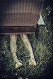 Jambes femelles sales collant de dessous un fauteuil dans un domaine, concept peu commun d'humeur foncée Photos libres de droits