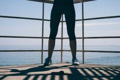 Jambes femelles sportives dans des espadrilles bleues et pantalon de survêtement contre Image stock
