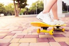 Jambes femelles sur la planche à roulettes Photo stock