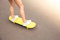 Jambes femelles sur la planche à roulettes Image stock