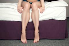 Jambes femelles toilettées dans le lit Image stock
