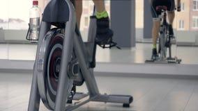Jambes femelles tournant des pédales sur le vélo statique dans la forme physique Formation de bicyclette dans le gymnase banque de vidéos