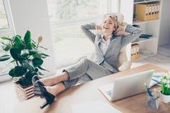 Jambes fraîches, gaies, souriantes de prise de directeur dans des chaussures sur la table, SI Images stock