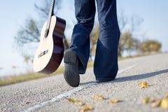 Jambes marchant loin avec la guitare de côté sur vide photos stock