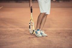 Jambes masculines avec la raquette de tennis Images stock